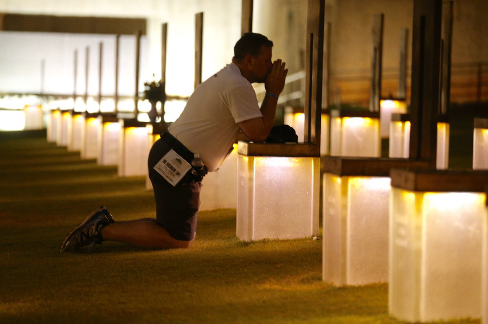 Photo - Kyle  Genzer prays at the chair of his mom Jamie fialkowski Genzer before the 20th Anniversary Remembrance Ceremony, Sunday, April 19, 2015, at the Oklahoma City National Memorial and Museum in Oklahoma City.