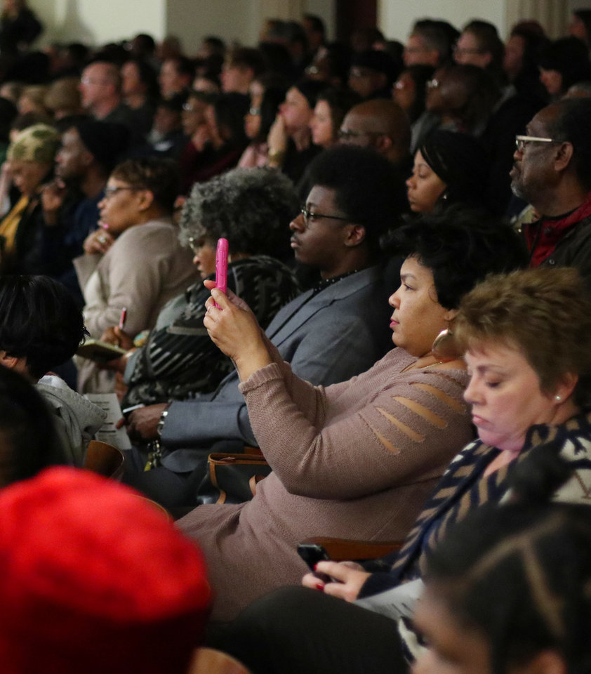 Photo - Attendees use their mobile phones to take photos of the graphics at the Oklahoma City School Board meeting, Tuesday, January 22, 2019.  Photo by Doug Hoke, The Oklahoman