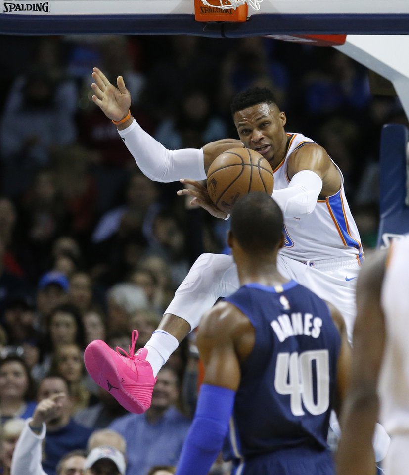 Photo - Oklahoma City Thunder guard Russell Westbrook (0) dunks in front of Dallas Mavericks forward Harrison Barnes (40) in the first half of an NBA basketball game in Oklahoma City, Monday, Dec. 31, 2018. (AP Photo/Sue Ogrocki)