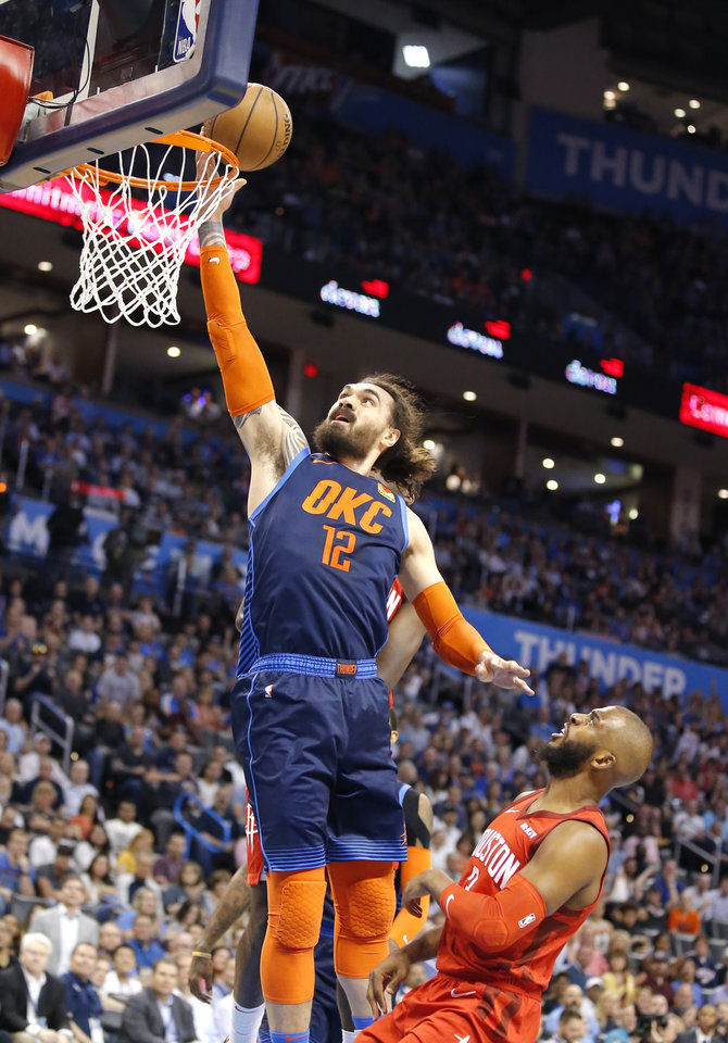 Photo -  Oklahoma City's Steven Adams, left, goes in for a layup as Houston's Chris Paul defends during Tuesday's game at Chesapeake Energy Arena. [photos by Sarah Phipps, The Oklahoman]