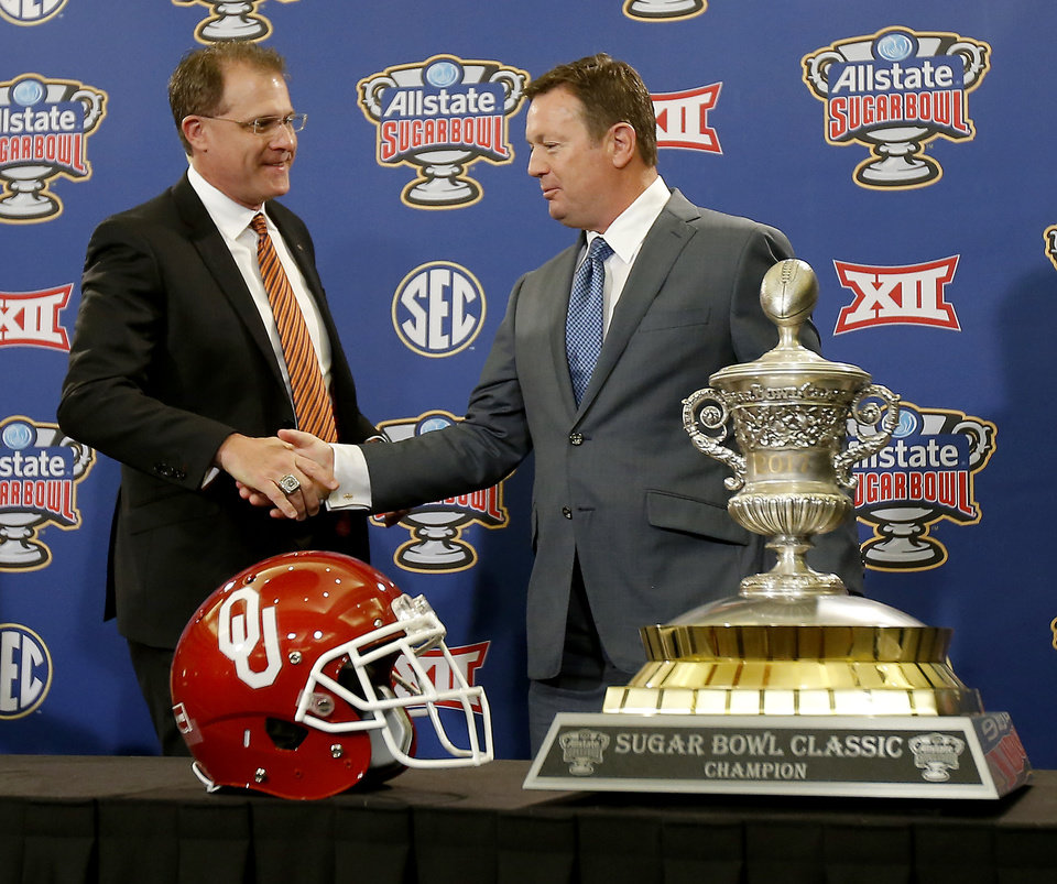 Photo - Oklahoma coach Bob Stoops, right,  and Auburn coach Gus Malzahn meet behind  the Sugar Bowl trophy during a press conference in New Orleans, Sunday Jan. 1, 2017. The University of Oklahoma football team will play Auburn in the Allstate Sugar Bowl on Monday, Jan. 2, 2017. Photo by Bryan Terry, The Oklahoman