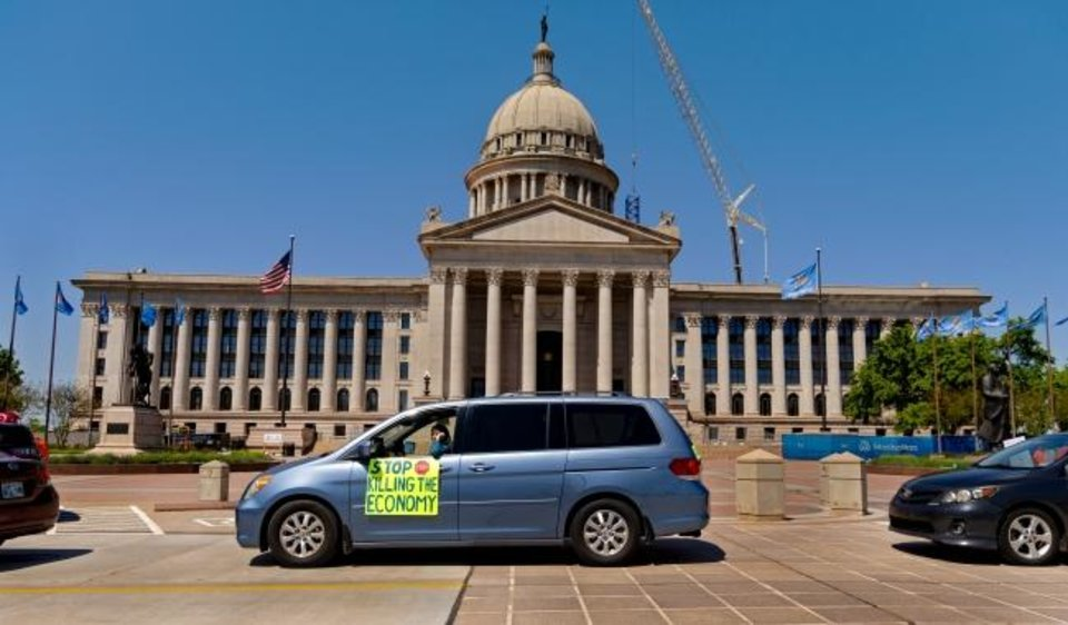 Photo -  A protester displays a sign out of the car window during the Let's Get Oklahoma Open For Business rally at the Oklahoma State Capitol in Oklahoma City, Okla. on Wednesday, April 15, 2020. Participants drove their cars around the Capitol to protest the hardship Oklahoma citizens are being placed in due to businesses being forced to close during the COVID-19 pandemic.  [Chris Landsberger/The Oklahoman]
