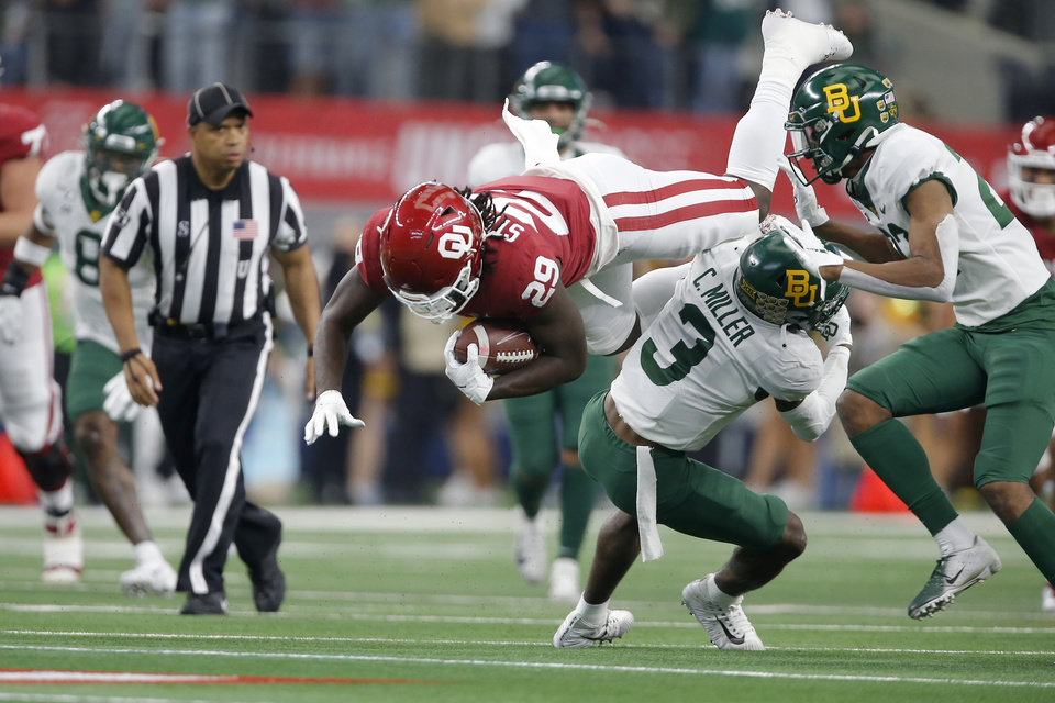 Photo - Oklahoma's Rhamondre Stevenson (29) leaps over Baylor's Chris Miller (3) during the Big 12 Championship Game between the University of Oklahoma Sooners (OU) and the Baylor University Bears at AT&T Stadium in Arlington, Texas, Saturday, Dec. 7, 2019. Oklahoma won 30-23. [Bryan Terry/The Oklahoman]