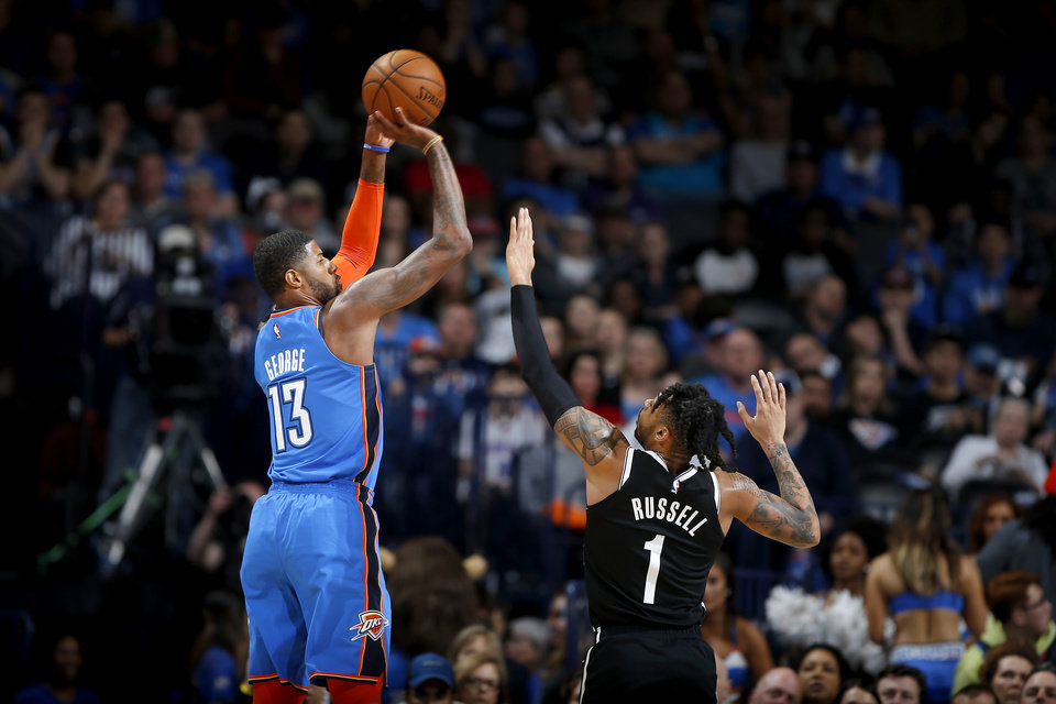 Photo - Oklahoma City's Paul George (13) shoots over Brooklyn's D'Angelo Russell (1) during an NBA basketball game between the Oklahoma City Thunder and the Brooklyn Nets at Chesapeake Energy Arena in Oklahoma City, Wednesday, March 13, 2019. Oklahoma City won 108-96. Photo by Bryan Terry, The Oklahoman