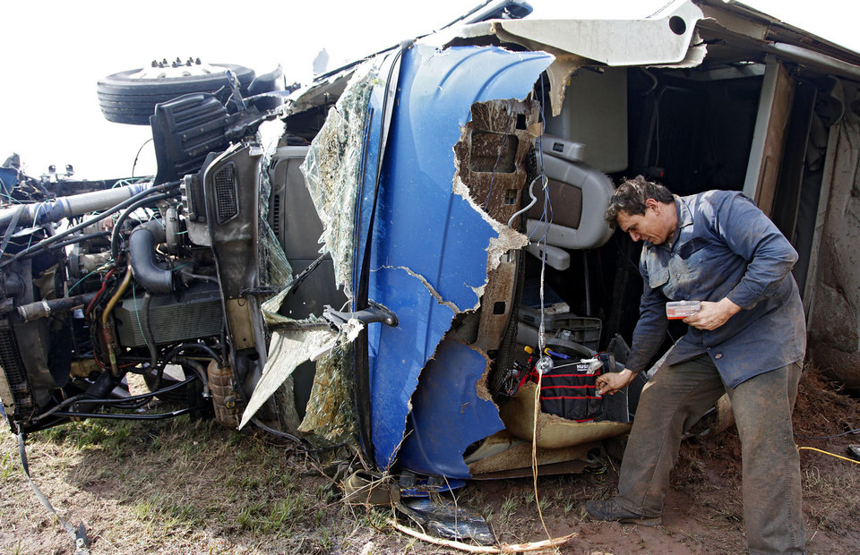 Photo - Armando Castillo finds personal items out of his truck that he was driving when it was swept off I-40 and destroyed by a tornado west of El Reno, Tuesday, May 24, 2011. Photo by Chris Landsberger, The Oklahoman ORG XMIT: KOD