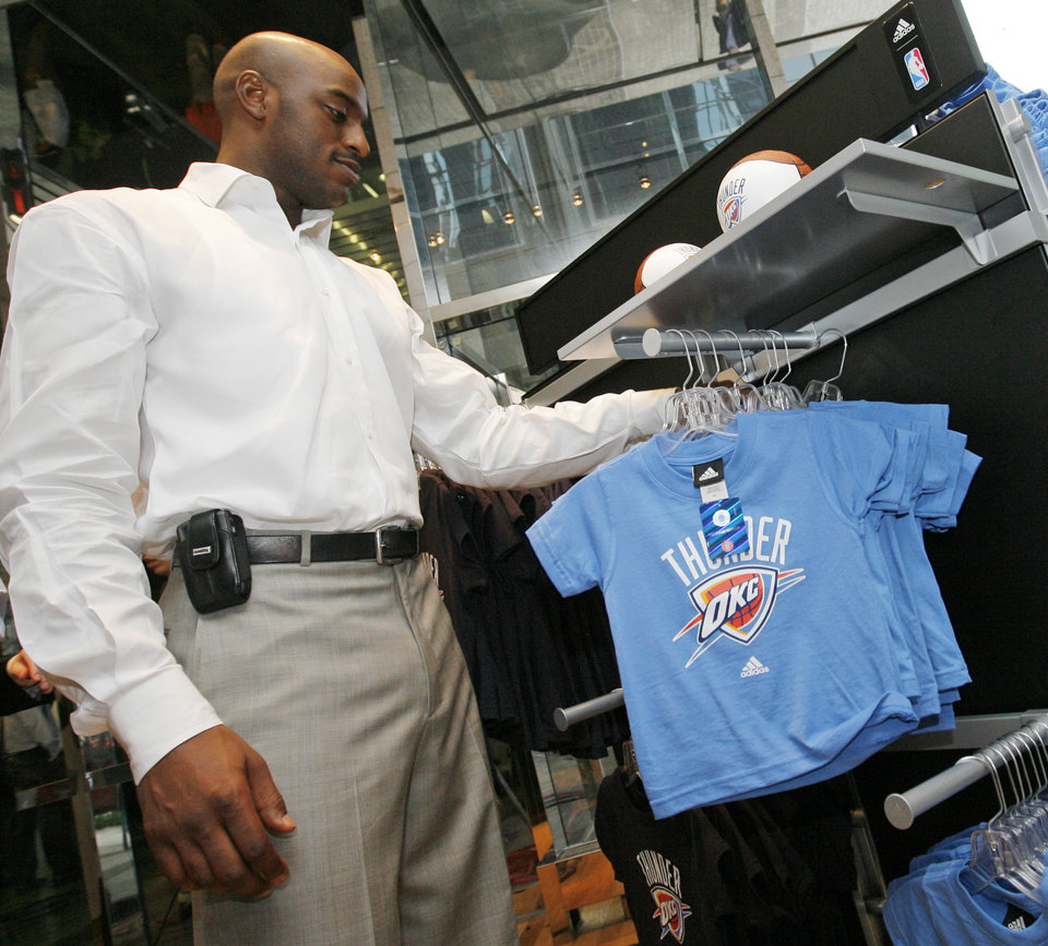 Photo - OKC Thunder player Damien Wilkins picks out shirts in the team store after the unveiling of the Oklahoma City Thunder NBA team name at Leadership Square in downtown Oklahoma City, Wednesday, September 3, 2008. NATE BILLINGS, THE OKLAHOMAN