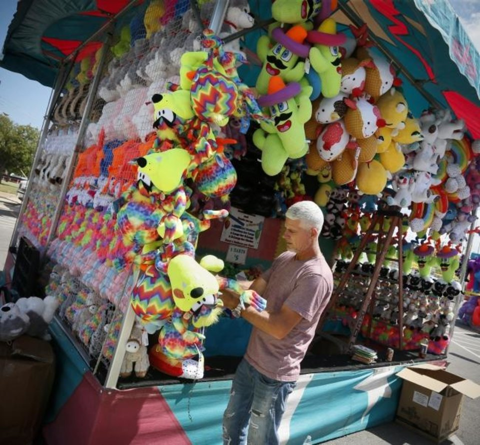 Photo -  James Cox attaches prizes to a game booth the day before the start of the Oklahoma State Fair at the OKC Fairgrounds in Oklahoma City, Wednesday, Sept. 11, 2019. [Nate Billings/The Oklahoman]