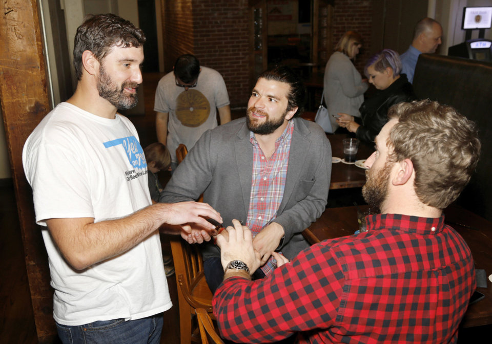 Photo -  Alex Weintz, from left, Nathan Enos and Charles Delhotal attend the Yes on 792 campaign's watch party at the Bricktown Brewery in Oklahoma City on Tuesday night. [Photo by Jim Beckel, The Oklahoman]