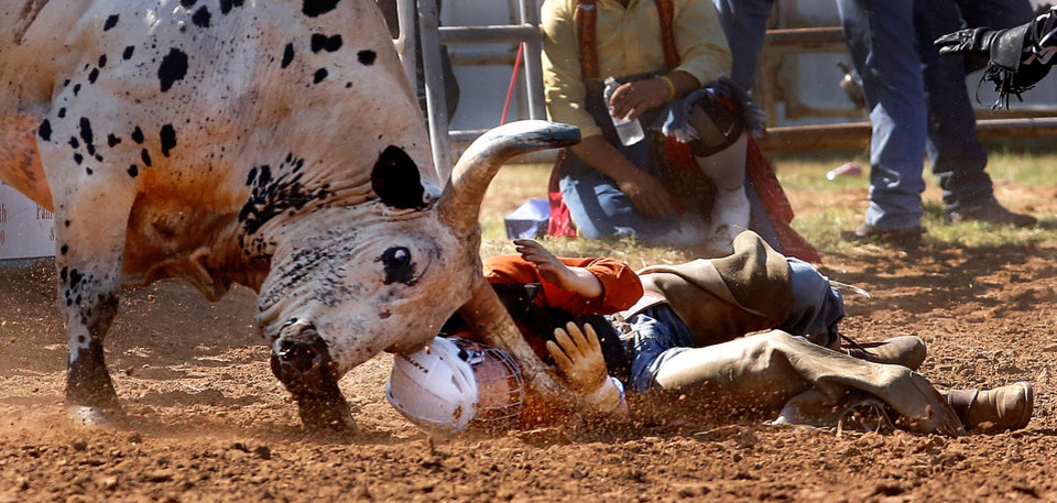 Photo -  A bull goes after rider Ty Duncan of Crossett, TX, after he was thrown from the animal during the  morning go-round of the IFYR Rodeo in Shawnee on Tuesday, July 9, 2013.  He was not injured. Photo  by Jim Beckel, The Oklahoman.