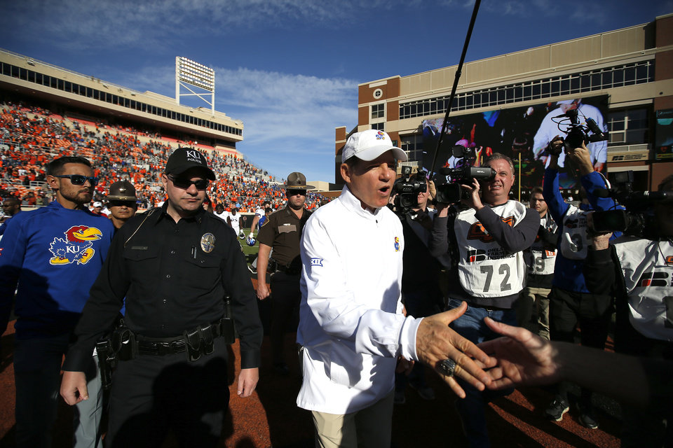 Photo - Kansas head coach Les Miles greets Oklahoma State head coach Mike Gundy following the college football game between the Oklahoma State University Cowboys and the Kansas Jayhawks at Boone Pickens Stadium in Stillwater, Okla., Saturday, Nov. 16, 2019. OSU won 31-13. [Sarah Phipps/The Oklahoman]