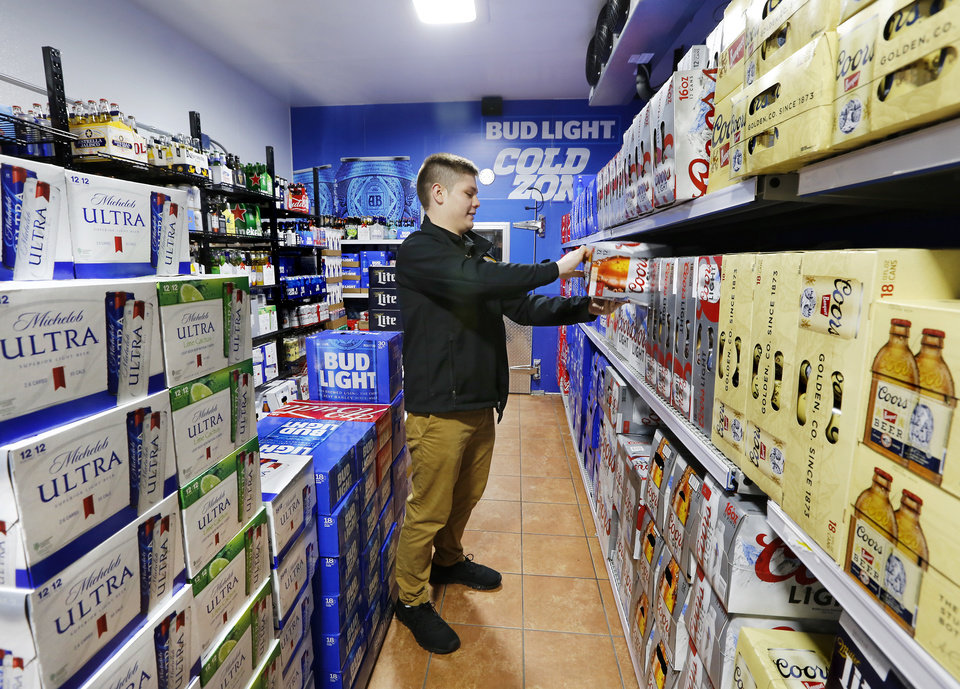 Photo -  OnCue clerk Braxtun Brown arranges products inside the store's Beer Cave Monday, Oct. 1, 2018. [Jim Beckel/The Oklahoman]