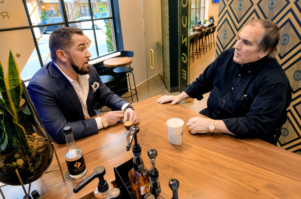 Photo -  Farmers Bank president and CEO Aaron Johnson, left, visits with his father Larry in the coffee bar at the bank's new branch location at 1300 N Walker Ave. [Photo by Chris Landsberger, The Oklahoman]