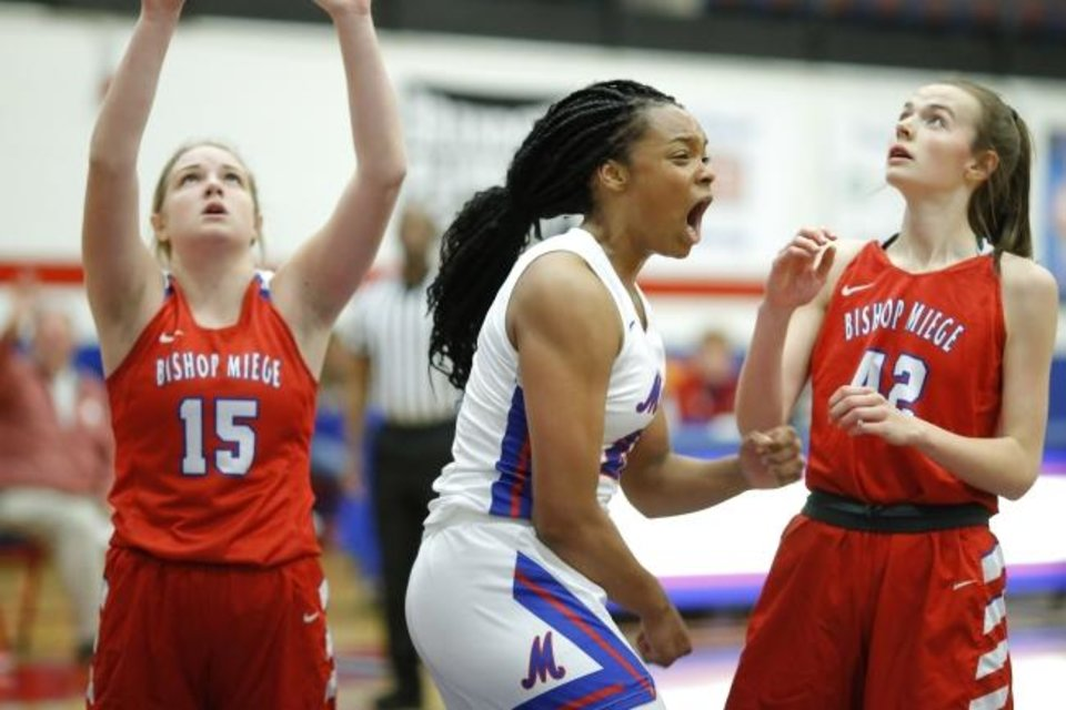 Photo -  Moore's Aaliyah Moore celebrates in front of Bishop Miege's Allie Burns, left. and Ashton Verhulst after making basket during a girls basketball game between Moore and Bishop Miege in Moore, Okla., Friday, Jan. 24, 2020. [Bryan Terry/The Oklahoman]