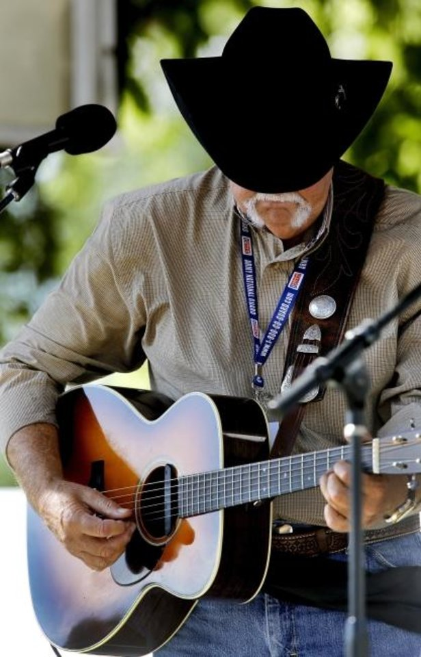 Photo -  Cowboy Jim Garling sings and plays the guitar during the 2013 International Bluegrass Festival in Cottonwood Flats Municipal Park in Guthrie. He will perform Saturday during the National Day of the Cowboy at the National Cowboy & Western Heritage Museum. [Jim Beckel/The Oklahoman Archives]