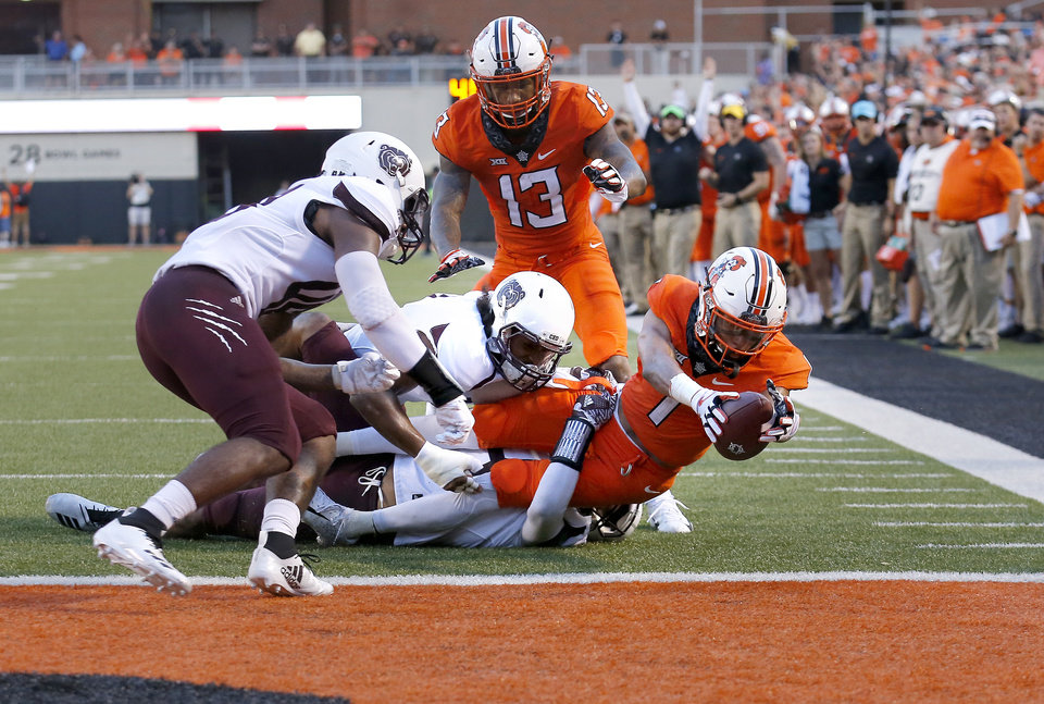 Photo - Oklahoma State's Jalen McCleskey (1) scores a touchdown as Missouri State's Kam Carter (47), Darius Joseph (2) and Tyler Lovelace (48) tackle him in the first quarter during a college football game between the Oklahoma State Cowboys (OSU) and the Missouri State Bears at Boone Pickens Stadium in Stillwater, Okla., Thursday, Aug. 30, 2018. Photo by Sarah Phipps, The Oklahoman