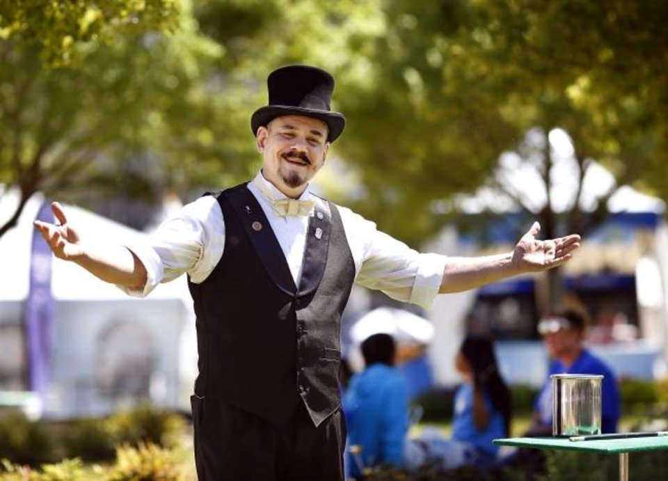 Photo -  Capstone the Magician, the official street performer at this year's Festival of the Arts, does a trick during a Thursday afternoon performance at the downtown Oklahoma City event. He is performing 40-minute sets at  at noon, 2:30 and 7:45 p.m. Friday and Saturday; and at noon, 2 and 4 p.m. Sunday.  Performances are on the Colcord Lawn at Bicentennial Park, near the Civic Center.   [Jim Beckel/The Oklahoman]