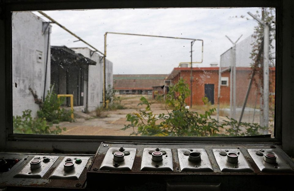 Photo -  In this Oct. 23, 2014, photo, buttons that used to open and close many of the gates sit with a view of some of the out buildings at the abandoned Central State Farm prison in Sugar Land, Texas. The unit was closed down four years ago. [Photo by Pat Sullivan, Associated Press]