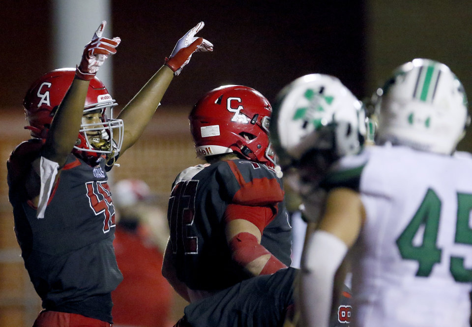 Photo - Carl Albert's Kentrell Bizzell, left, celebrates a touchdown during Friday's game against McGuinness in Midwest City. [Sarah Phipps/The Oklahoman]