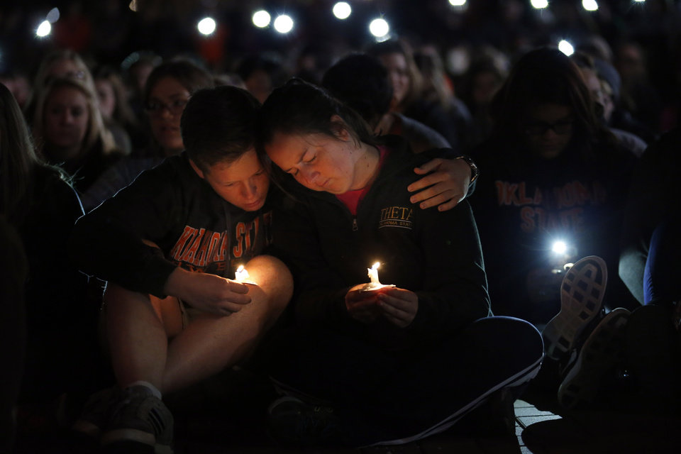 Photo - Students pray during a candle light vigil on the campus of Oklahoma State University,  Sunday, Oct. 25, 2015. The community gathered on the campus to remember those affected by the homecoming fatality crash. Photo by Sarah Phipps, The Oklahoman