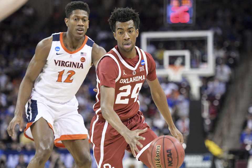 Photo - Oklahoma guard Jamal Bieniemy (24) dribbles the ball against Virginia guard De'Andre Hunter (12) during the first half of a second-round game in the NCAA men's college basketball tournament Sunday, March 24, 2019, in Columbia, S.C. (AP Photo/Sean Rayford)