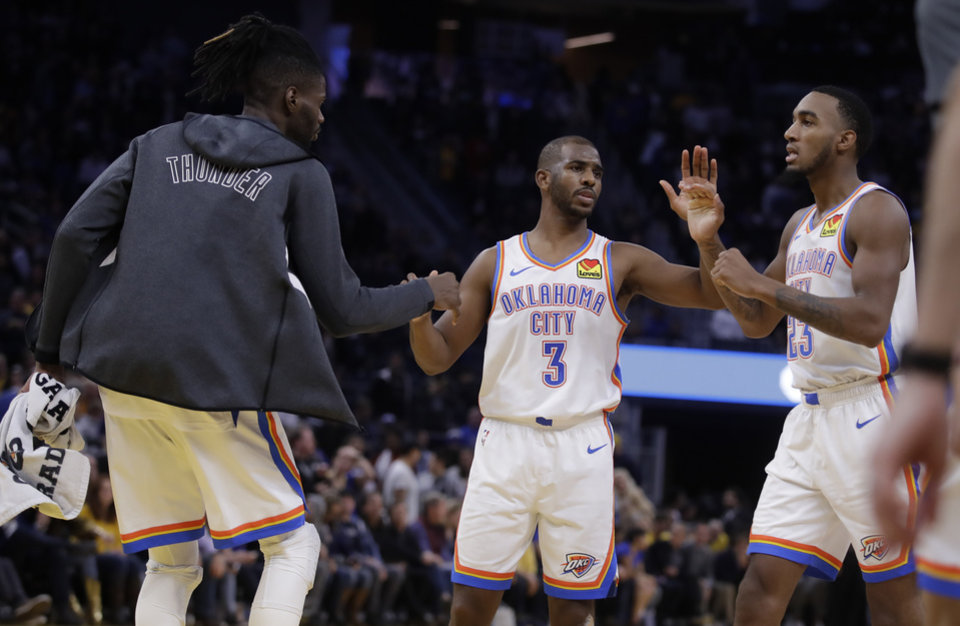 Photo - Oklahoma City Thunder guard Chris Paul (3) celebrates with Nerlens Noel, left, and Terrance Ferguson (23) at the end of an NBA basketball game against the Golden State Warriors Monday, Nov. 25, 2019, in San Francisco. (AP Photo/Ben Margot)