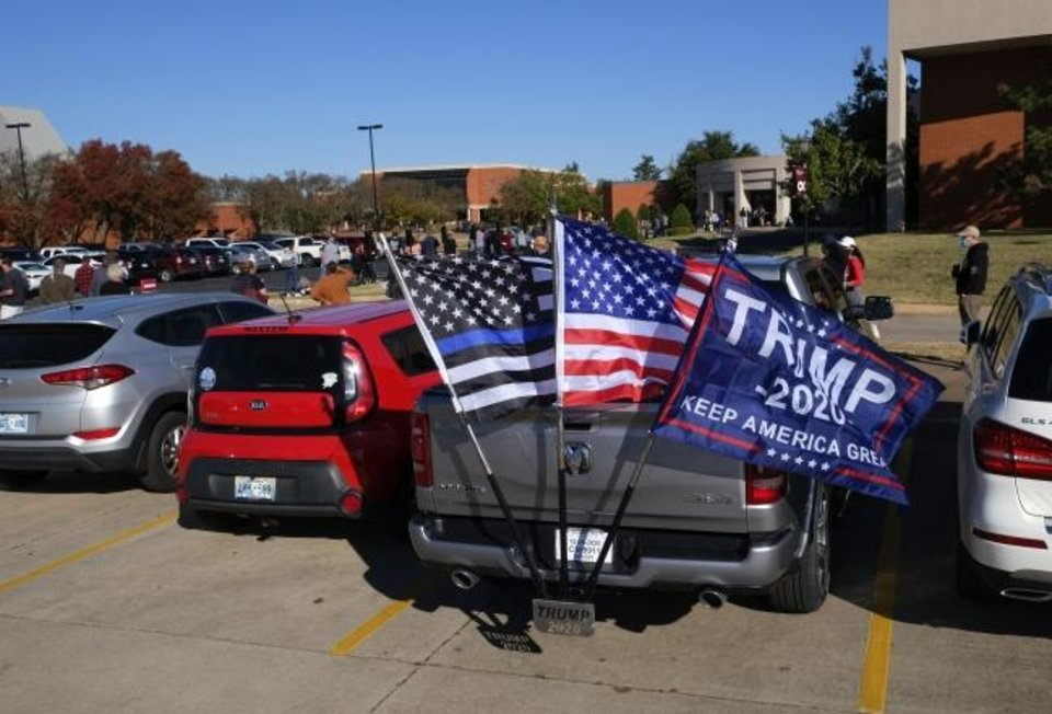 Photo -  A pickup truck with a Trump 2020 flag sits in the parking lot of a polling place at Oklahoma Christian University on Tuesday. [Doug Hoke/The Oklahoman]