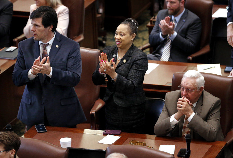Photo -  Representative William Fourkiller, Sen. Anastasia Pittman and Rep. Steve Kouplen listen as Gov. Mary Fallin gives her final State of the State address in the chambers of the Oklahoma House of Representatives on Monday. [Photo by Steve Sisney, The Oklahoman]
