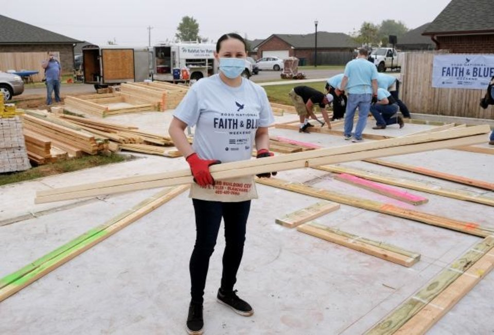 Photo -  Elizabeth Martinez is shown at the Habitat for Humanity home site for her new house as Oklahoma City Police Department officers and employees work with church members on the project as part of