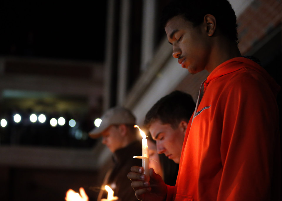 Photo - Oklahoma State University freshman Bryce Jones prays during a candle light vigil on the campus of OSU,  Sunday, Oct. 25, 2015. The community gathered on the campus to remember those affected by the homecoming fatality crash. Photo by Sarah Phipps, The Oklahoman