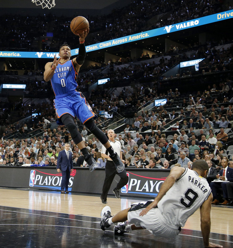 Photo - Oklahoma City's Russell Westbrook (0) knocks down San Antonio's Tony Parker (9) as he is called for an offensive foul during Game 5 of the second-round series between the Oklahoma City Thunder and the San Antonio Spurs in the NBA playoffs at the AT&T Center in San Antonio, Tuesday, May 10, 2016. Oklahoma City won 95-91. Photo by Bryan Terry, The Oklahoman