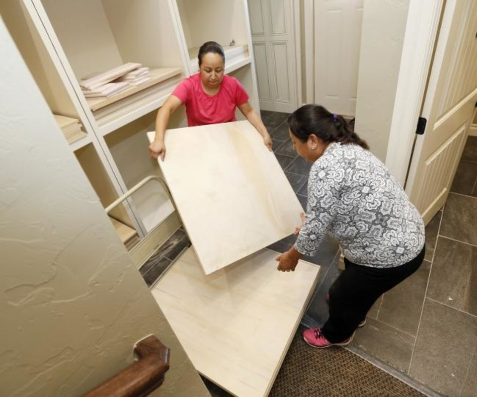 Photo -  Adriana Vidales, left, and Guadalupe Monter move boards to be painted inside the new UBuildIt office building at 5120 Gaillardia Corporate Place. [NATE BILLINGS/THE OKLAHOMAN]