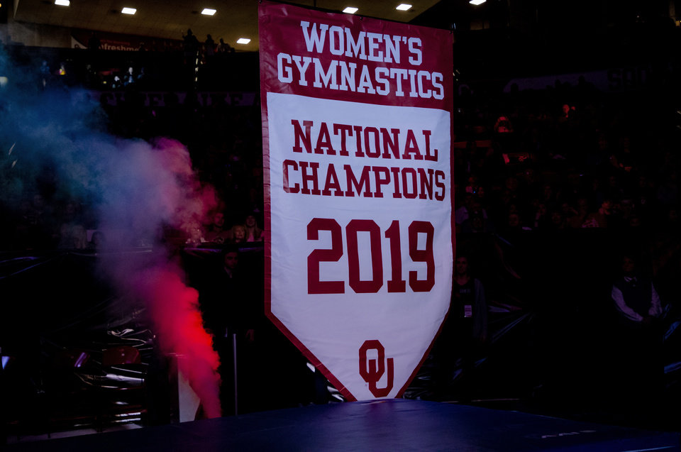 Photo - The University of Oklahoma 2019 Women's Gymnastics National Champions banner is raised to the rafters before the start of the women's gymnastics competition between the University of Oklahoma and Arkansas at the Lloyd Noble Center in Norman, Okla Monday, Jan. 20, 2020.   [Chris Landsberger/The Oklahoman]