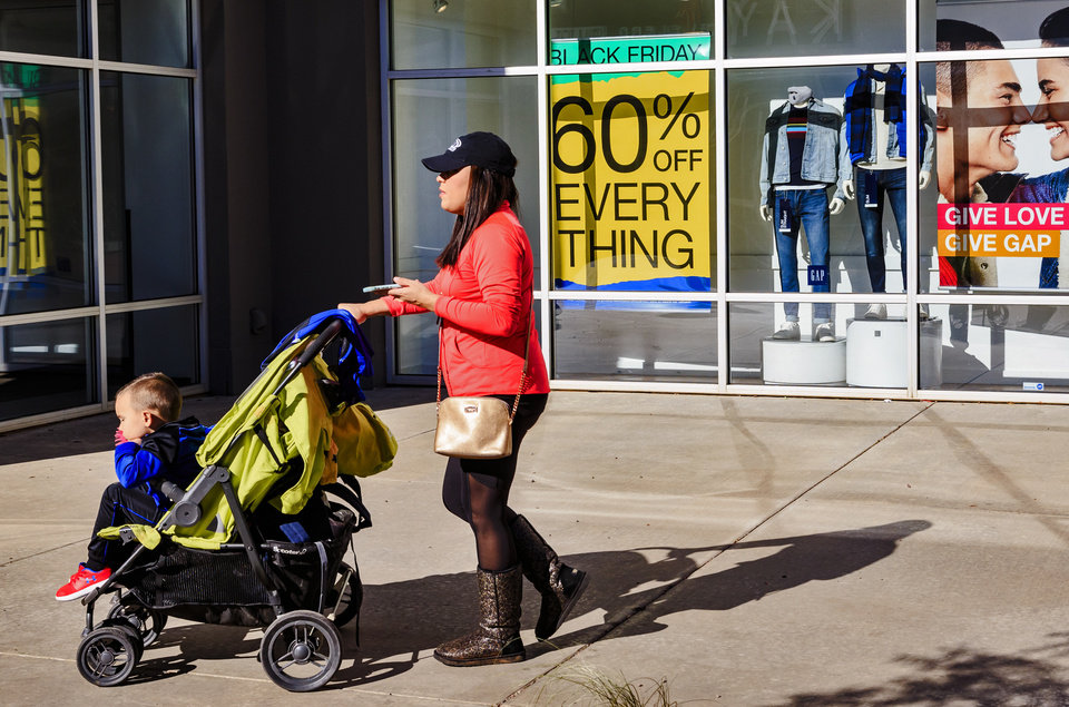 Photo -  Customers walk past Black Friday sale signs at the OKC Outlet Mall in Oklahoma City on Tuesday. [Photo by Chris Landsberger, The Oklahoman]