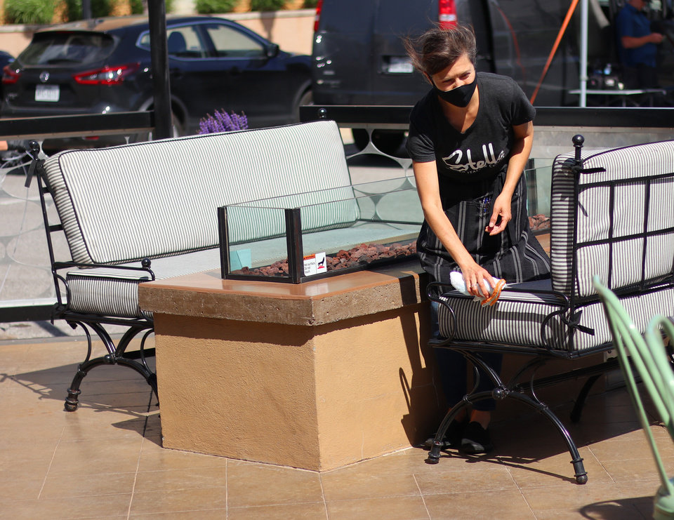 Photo - An employee wipes down seating after customers left at Stella Modern Italian has started limited service back up, keeping dine in customers on the patio, Friday, May 1, 2020. [Doug Hoke/The Oklahoman]