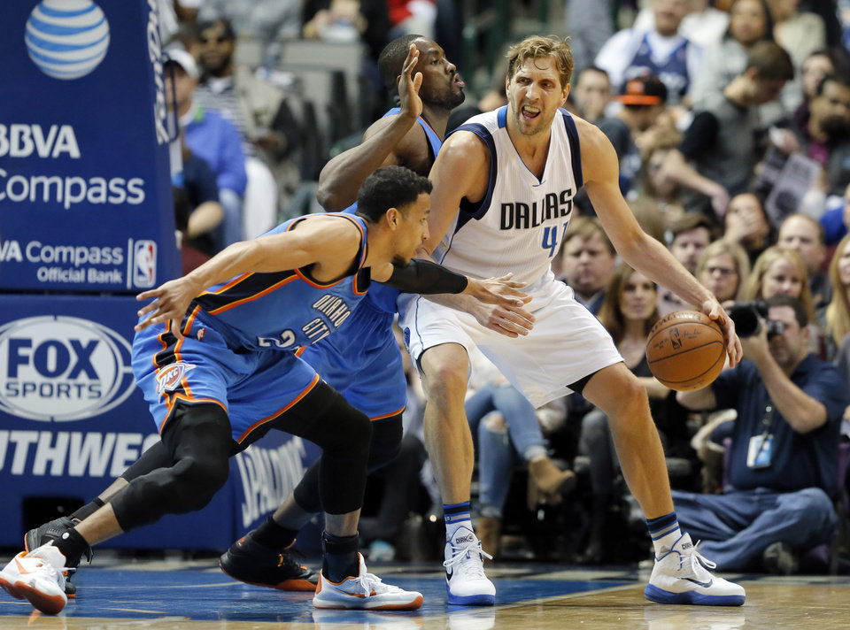 Photo - Oklahoma City Thunder's Andre Roberson (21) and Serge Ibaka, rear, defend as Dallas Mavericks forward Dirk Nowitzki (41) of Germany positions for a shot opportunity in the first half of an NBA basketball game, Wednesday, Feb. 24, 2016, in Dallas. (AP Photo/Tony Gutierrez)