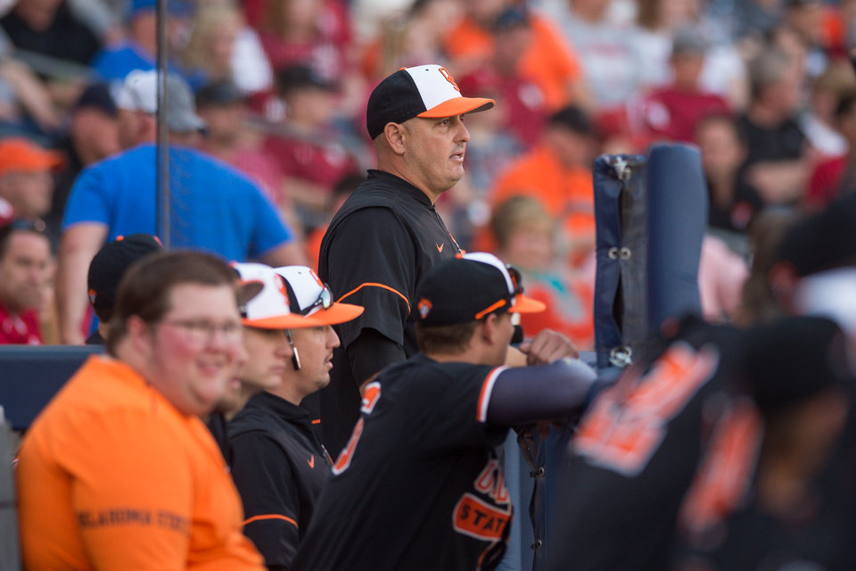Photo - Oklahoma State head coach Josh Holliday (center) looks on from the dugout during the game against Oklahoma at ONEOK Field in Tulsa, OK on 4/28/18.  BRETT ROJO/For the Tulsa World