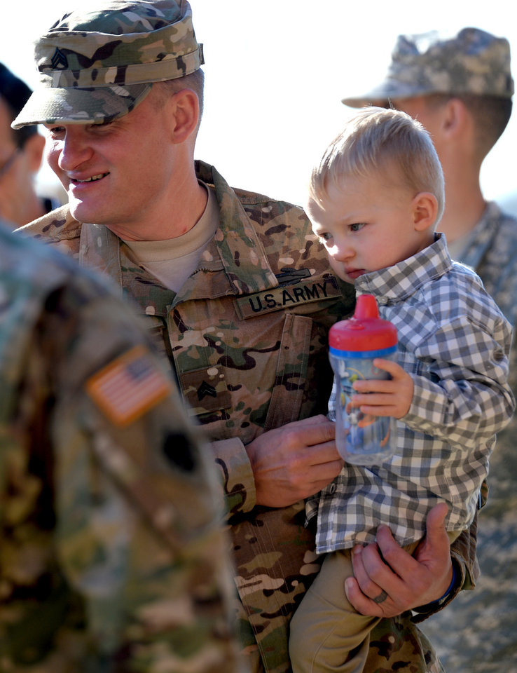 Photo -  Sgt. Brent Simmons holds his son, Blayze, before saying goodbye during a sendoff ceremony for members of the Oklahoma National Guard's 1st Battalion, 179th Infantry Regiment at First Baptist Church of Moore. The battalion is deploying to Ukraine early next year. [Photo by Jackie Dobson, for The Oklahoman]