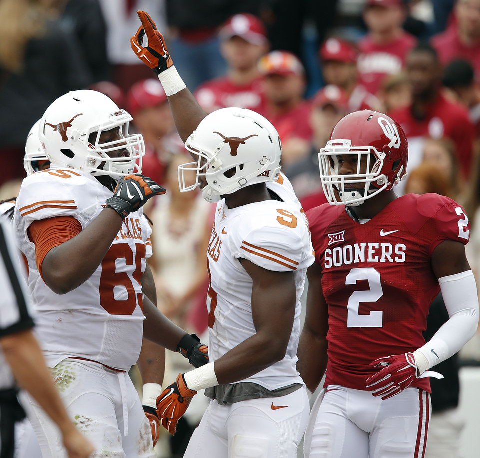 Photo - Texas' Marcus Hutchins (65) and John Harris (9) celebrate a touchdown in front of Texas' Mykkele Thompson (2) during the college football game between the University of Oklahoma Sooners (OU) and the University of Texas Longhorns (UT) during the Red River Showdown at the Cotton bowl in Dallas, Texas on Saturday, Oct. 11, 2014. Photo by Chris Landsberger, The Oklahoman