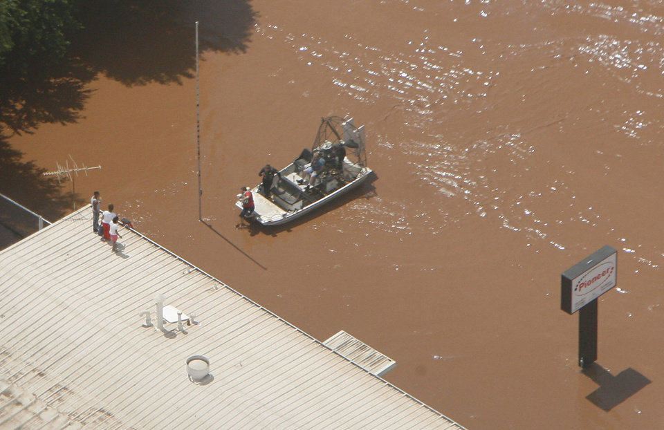 Photo - Flooding in Kingfisher after tropical storm Erin hit the area early Sunday, Aug. 19, 2007. Resuers on an airboat check on people on the roof of a business.  BY MATT STRASEN, THE OKLAHOMAN/KWTV SKYNEWS 9