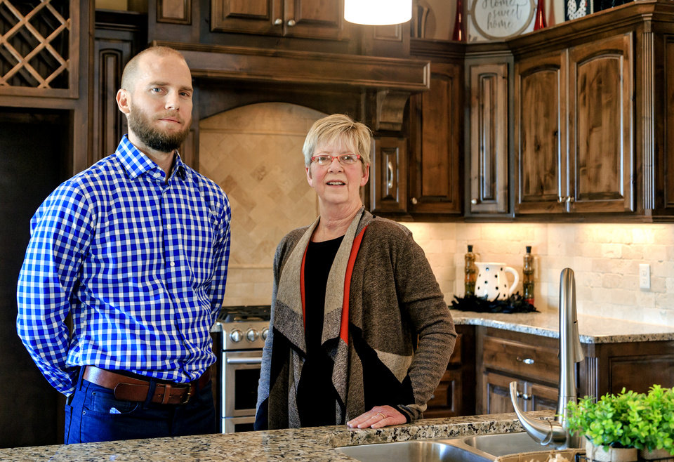 Photo -  Timber Crest developer Zach Holland, of Premium Land LLC, left, and Jim Campbell Homes sales and marketing manager Diane Campbell show the kitchen in a Jim Campbell parade home at 3208 Drake Crest Drive in Edmond. [PHOTO BY CHRIS LANDSBERGER, THE OKLAHOMAN]