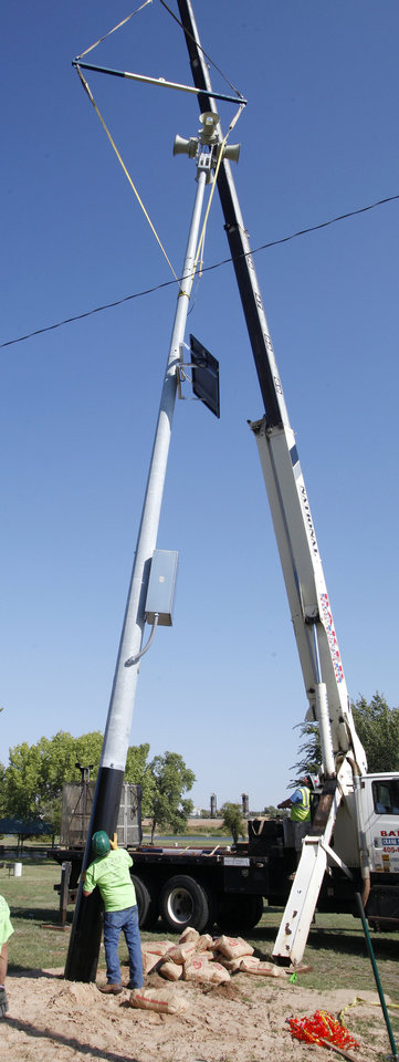 Photo - A new siren is installed at Eagle Lake in Del City on Wednesday. Del City is installing eight new sirens around town. Photo by Paul B. Southerland, The Oklahoman  PAUL B. SOUTHERLAND - PAUL B. SOUTHERLAND