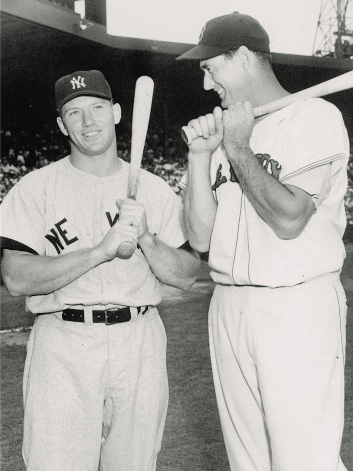 Photo - Mickey Mantle of the New York Yankees, and Ted Williams of the Boston Red Sox, carry weapons that made them famous during a conversation before a doubleheader in this July 4, 1956 photo at Boston's Fenway Park. (AP Photo)