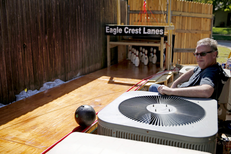 Photo - Heath Jones watches a ball return on a bowling lane in the backyard of his Oklahoma City home, Tuesday, April 21, 2020. Health Jones and his son Eric built a bowling lane in their backyard so that Eric, a competitive bowler, could continue to bowl while bowling alleys are closed.. [Bryan Terry/The Oklahoman]