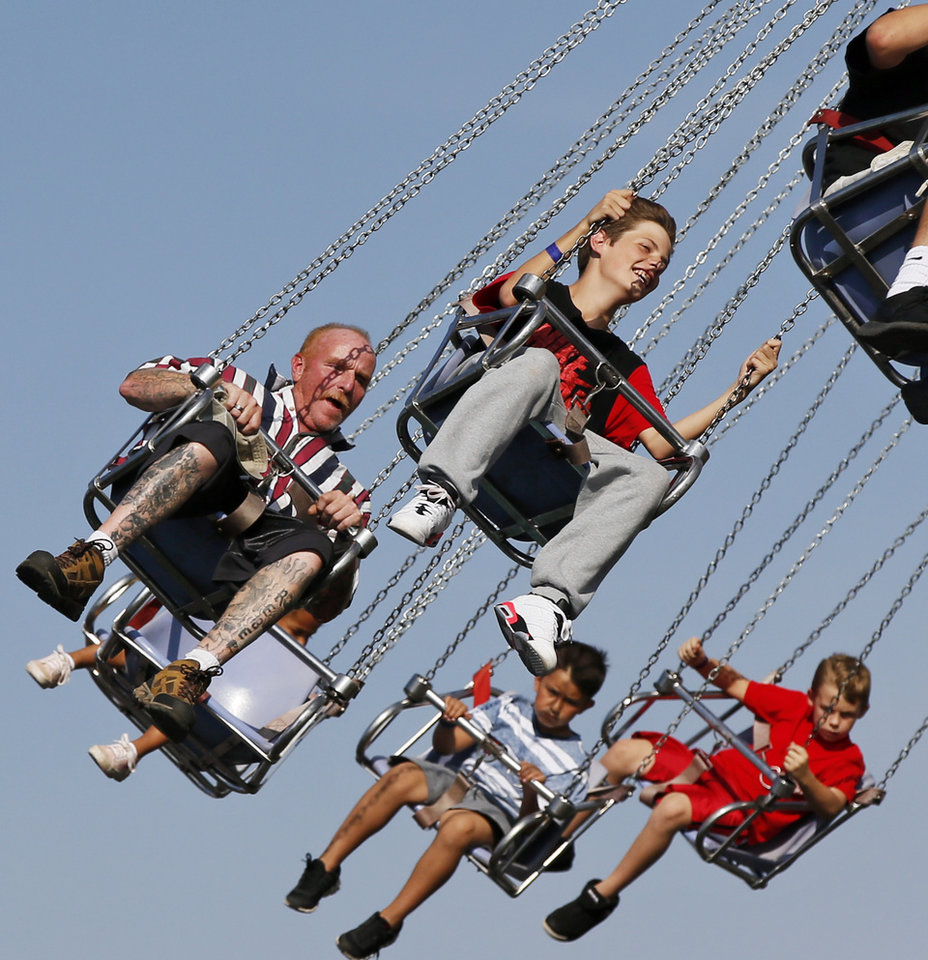 Photo -  People ride on swings Sept. 27, 2015, during the Oklahoma State Fair at State Fair Park. [Photo by Nate Billings, The Oklahoman Archives]