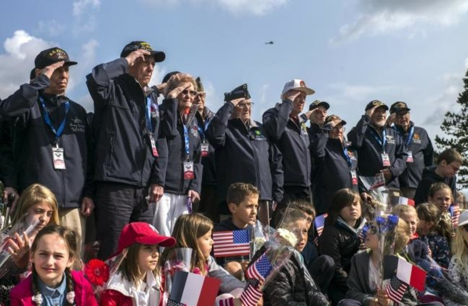 Photo -  World War II veterans from the United States salute as they pose with localschool children at the Normandy American Cemetery in Colleville-sur-Mer, Normandy, France on Monday. France is preparing to mark the 75th anniversary of the D-Day invasion which took place on June 6, 1944. [AP Photo/Rafael Yaghobzadeh]