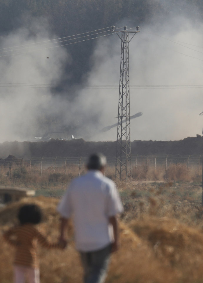Photo -  People walk in Akcakale, Sanliurfa province, southeastern Turkey, as in the background, Turkish forces artillery pieces fire targets towards Syria, Friday, Oct. 11, 2019.(AP Photo/Lefteris Pitarakis)