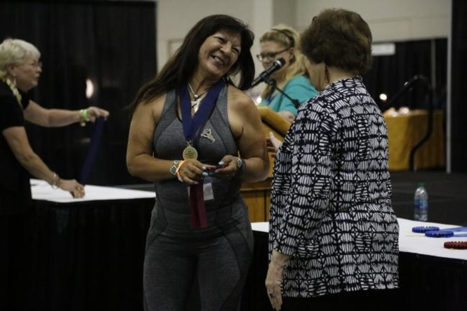 Photo -  Rosemary Hill, left, receives the Dana and Terry Brown Award for Best of Show from Red Earth Board President Lona Barrick of the 2019 Red Earth Festival at the Cox Convention Center in Oklahoma City, Oklahoma Friday, June 7, 2019.  [Paxson Haws/The Oklahoman]