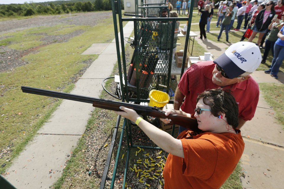 Photo -  Retired Oklahoma County District Judge Chuck Black assists 16-year-old Sydney Baxter on the shotgun range at the OKC Gun Club. (Photo by Paul Hellstern, The Oklahoman)