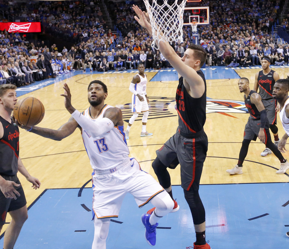 Photo - Oklahoma City's Paul George (13) goes up for a basket as Portland's Zach Collins (33) defends during the NBA basketball game between the Oklahoma City Thunder and the Portland Trail Blazers at Chesapeake Energy Arena in Oklahoma City, Tuesday, Jan. 22, 2019. Photo by Sarah Phipps, The Oklahoman