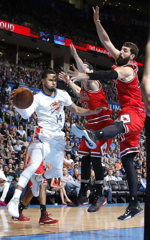 Photo - Oklahoma City's D.J. Augustin (14) passes the ball around Chicago's Kirk Hinrich (12) and Chicago's Nikola Mirotic (44) during the NBA game between the Oklahoma City Thunder and the Chicago Bulls at Chesapeake Energy Arena in Oklahoma City, Sunday, March  15, 2015. Photo by Sarah Phipps, The Oklahoman